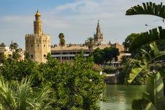 Seville Spanien - Sept 23 2013: Torre del Oro med laen Giralda i avståndet och floden i förgrunden royaltyfri bild