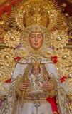 Seville - tradicional vested Madonna staty (Virgen del Rocijo) vid S S Rojas från sidoaltaret i barockkyrka av El Salvador Arkivbild