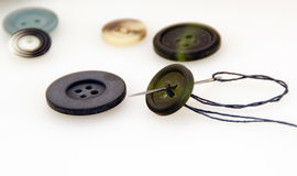 Sew a button. With a needle and thread stock images