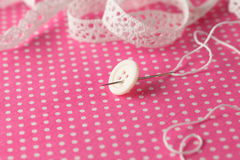 Sew on button on polka dot cloth Royalty Free Stock Images