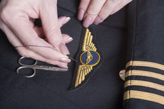 Sew pilot wings onto uniform Royalty Free Stock Photos