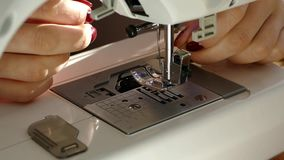 Sew on the sewing machine. A woman with a manicure reinforces the thread in the needle. stock footage
