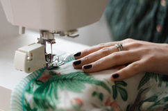 Sew on a sewing machine. Woman sews on the sewing machine clothing Stock Images