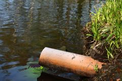 Sewage. A photo of an orange pipe and a polluted pond Stock Photo