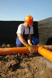 Sewage assembly. Plumber assembling pvc sewage pipes in house foundation Stock Photography