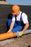 Sewage assembly. Plumber assembling pvc sewage pipes in house foundation Royalty Free Stock Image