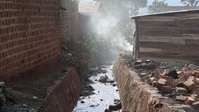 Sewage Ditch in African Town as Smoke Comes Out of Home Nearby