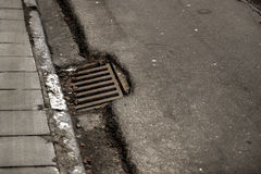 Sewage hole on the road Royalty Free Stock Images