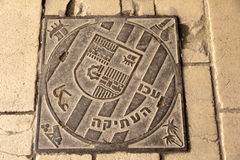 Ancient Acco Sewage Lid. Sewage lid with the emblem of the ancient city of Acco (Acre, in Israel) inscribed on it. The text in Hebrew and Arabic trnaslates to Stock Image