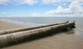 Sewage pipe draining into the ocean. A pristine beach view ruined by a polluting pipe draining into it stock images