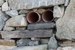 Sewage pipe in the stone wall Royalty Free Stock Images