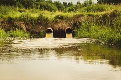 sewage from the sewer pollutes a lake/Waste water flow from water pipe into lake stock photos