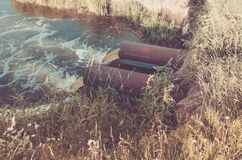 sewage from the sewer pollutes a lake/water gushing from the sewer to the river. Toned royalty free stock image