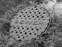 Sewer Cover (B&W). Cover over a Sewer Opening (Black & White) (B&W stock photography
