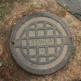 Sewer cover. Metal sewer cover beside path in park stock photography