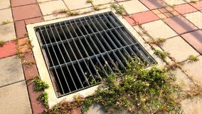 Sewer cover near tennis court Royalty Free Stock Photo