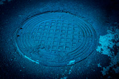 Sewer Cover. Round sewer cover on wet rough asphalt street Royalty Free Stock Photo