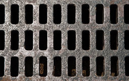 Sewer Drain. A top view of an old iron sewer drain cover filled with slots Stock Images