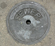 Sewer Drain Pipe in Street. Sewer drain cap in the middle of the street stock photos