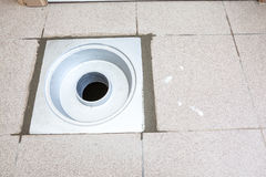 An sewer drain. There is a sewer drain in the ground with cement fattene Royalty Free Stock Image