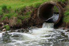 Sewer drains flow to the river Stock Photos