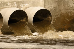 Sewer drains. Toxic water running from sewers to the environment Royalty Free Stock Photo