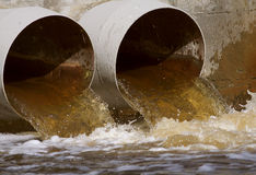 Sewer drains. Toxic water running from a sewer to the river Royalty Free Stock Images