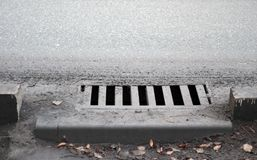 Sewer by footpath. Stormwater street drain stock photo