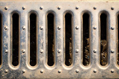 Sewer grate. That drains water from a parking lot. Selective focus Stock Photos