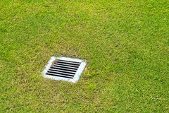 The sewer grate. On the lawn - drainage for heavy rain Royalty Free Stock Image