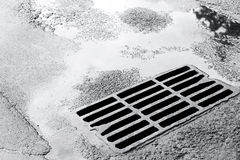 Sewer grate on wet road with puddles Royalty Free Stock Photos