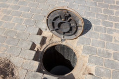 Sewer hole in a brick road Stock Photos