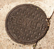 Sewer hole cover located in street Royalty Free Stock Photo