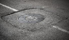 Sewer manhole cover on asphalt Stock Photography