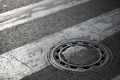 Sewer manhole cover on dark asphalt Royalty Free Stock Image