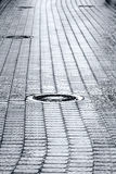 Sewer manhole cover on wet cobblestone street Stock Image