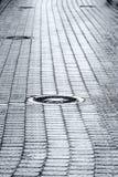 Sewer manhole cover on wet cobblestone street Stock Image