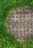 Sewer manhole with grass and word danger Royalty Free Stock Photos