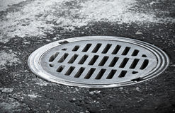 Sewer manhole on the urban asphalt road Royalty Free Stock Image