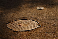 Sewer manholes on asphalt pavement Stock Photography