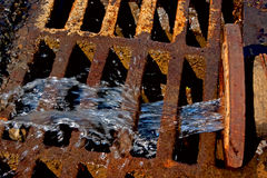Sewer pipe with liquid waste flowing out Stock Photo