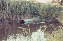 Sewer pipe pour out to the lake/ecology concept: Waste water flow from water pipe into lake stock images