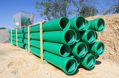 Sewer pipes. Pallets of green sewer pipes at construction site royalty free stock images