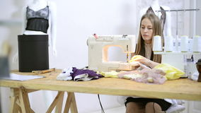 Sewer putting thread in sewing machine preparation in atelier stock footage