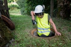 Sewer repair works in the manhole by a woman worker. Woman worker goes underground on the manhole for sewer repair work royalty free stock photo