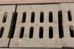 Sewer System Concrete Road Grid Grate Blocks For Drain Rain Water Photo Shot. Sewer System Concrete Road Grid Grate Blocks For Drain Rain Water Photo royalty free stock image