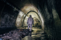 Sewer tunnel worker in chemical protective suite in underground gassy sewer tunnel. Sewer tunnel worker in special chemical protective suite in underground gassy royalty free stock images