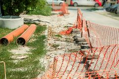Sewerage and water supply system pipes replacement construction site on the street in the city with new pipeline prepared for inst. Alling underground and orange royalty free stock photography