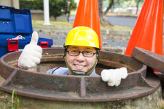 Sewerage worker in the manhole Stock Image