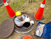 Sewerage worker in the manhole. With thumb up Stock Photos